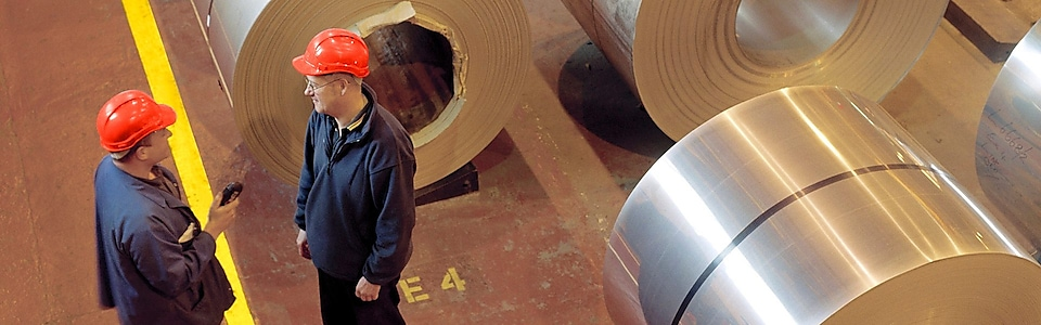 Two factory workers talking next to large rolls of steel